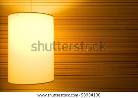 Lamp on a textured wallpaper shining. Including copy space.