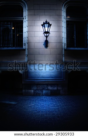 lamp on the brick wall in old european city - stock photo