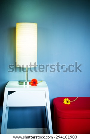 Lamp on white table next to red seat & flowers in living room at night for interior background