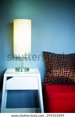 Lamp on white table next to red seat & pillow in living room at night for interior background