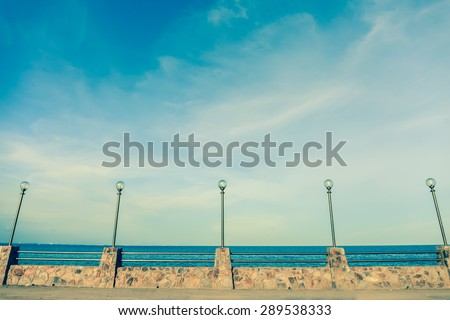 Lamp post and stone fence on road beside blue sea in vintage style