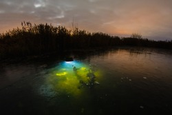 Lamp which illuminating underwater plant under the ice at the background of winter night landscape with frozen lake