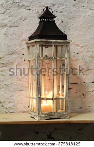 lamp with a candle on the shelf background stone wall #375818125