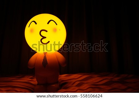 Lamp yellow round  face emoticon kiss a black background #558106624