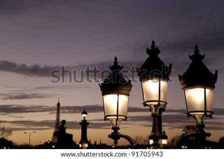 Lamppost illuminated at night and Eiffel Tower in Paris, France