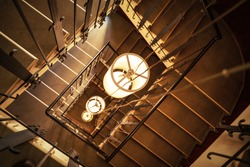 Lamps on long wires hang down to first floor from flight of stairs, top view. Labyrinth of stairs with beautiful railings in mansion or in boutique hotel. Interior design and architecture of building