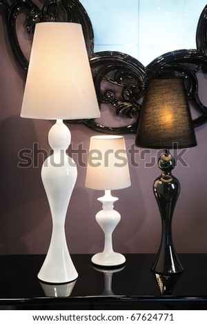 lamps over a buffet with a reflection and a vintage mirror in background