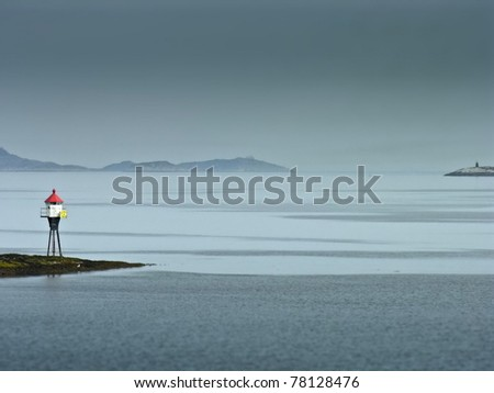 Land marker buoy in norway sea in a foggy day