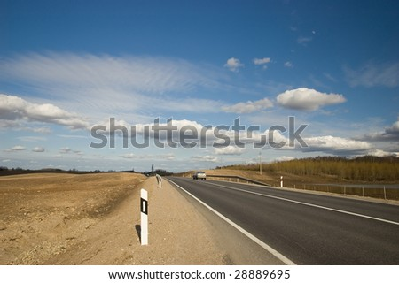 land road with going car and deep blue sky - stock photo