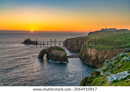 Land's End at sunset with Enys Dodman arch, Cornwall