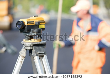 Land surveying equipment theodolite at construction site on industrial worker background during road works