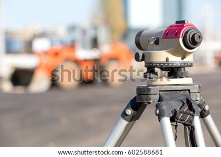 Land surveying equipment theodolite at construction site on wheel loader machine background