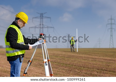Land surveyors on construction site reading plans wear for How to read construction site plans