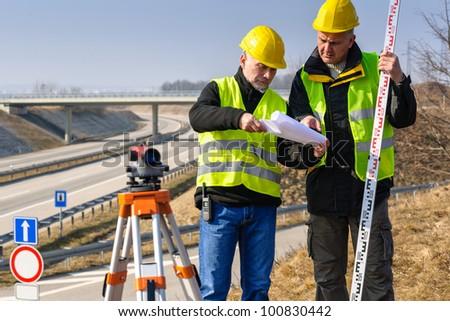 Land surveyors on highway reading geodesist plans use tacheometer - stock photo