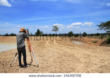 Land surveyors using camera on construction site