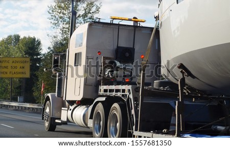 Land transport of boats and yachts. Truck with a special trailer for boat transport. stock photo