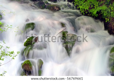 land which is fresh water with a waterfall and rushing noise coming from the Alps