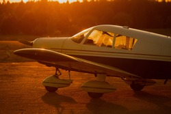 Landed small four-seater airplane at sunset background.