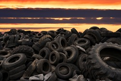 Landfill with old tires and tyres for recycling. Reuse of the waste rubber tyres. Disposal of waste tires. Worn out wheels for recycling. Tyre dump burning plant. Regenerated tire rubber produced.