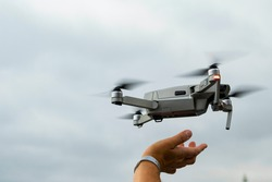 Landing a drone on your hand. It shows a man's hand and a quadrocopter descending on it. Copy space.