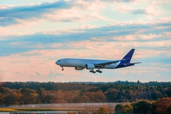 Landing airplane in the morning.Landscape with front of big airplane is flying over runway and trees in autumn.Travel background. Passenger plane. Commercial aircraft. Private jet