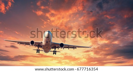 Landing airplane. Landscape with white passenger airplane is flying in the orange sky with clouds at colorful sunset. Travel background. Passenger airliner. Business trip. Commercial aircraft. Concept