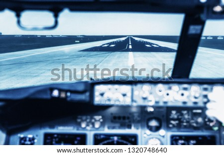 Landing course seen from the cockpit. A view from the cockpit of a large transport aircraft to the runway. A view of the cockpit of a large commercial airplane, a cockpit trainer. #1320748640
