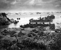 Landing craft of supply U.S. forces on Okinawa, 13 days after the initial invasion. Beyond are U.S. battlewagons, cruisers and destroyers. April 13, 1945.