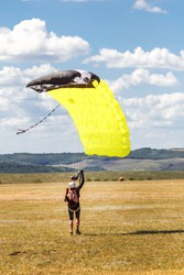 Landing. Freedom as a way of life. Skydiver landed in the field. Parachutist in professional equipment. Team of active sports.