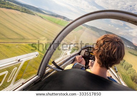 Photo of  Landing of plane with pilot on natural airport, Pilot in cockpit of plane during landing, Flying small sailplane with pilot