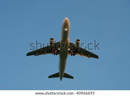 Landing plane against dusk sky