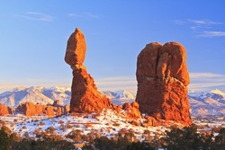 Landmark Balanced Rock perched on a snowy hill against the backdrop of the snow-capped La Sal Mountains in Arches National Park, Utah