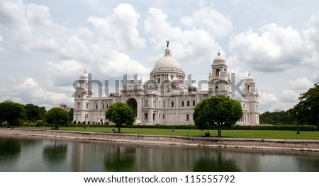 Landmark building of Calcutta (aka Kolkata), Victoria Memorial Hall with Queen's Garden in the foreground, pond, white Marble, cloudy sky