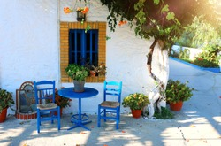 landmark photo of blue chairs with table in typical Greek town