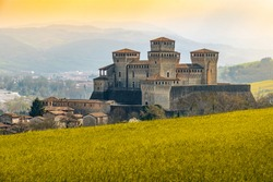 landmarks of italy, the Torrechiara fantasy castle near Parma - Italy with yellow warm toned grass and sky vintage look with copy space .