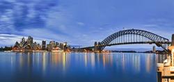 Landmarks of Sydney city CBD across Harbour with bridge, circular quay, passenger terminal and downtown skyscrapers to Kirribilli pier at blue cloudy sunrise.