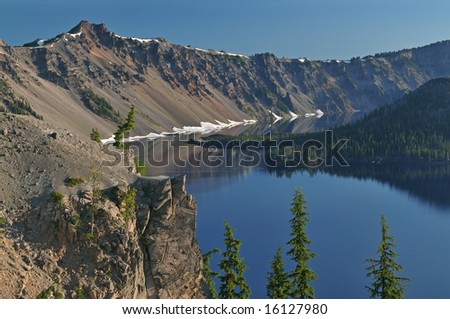 Landscape at sunrise of Crater Lake National Park with conifers, Wizard Island, and crater rim, Oregon, USA