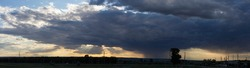 Landscape at sunset. A thunderstorm is approaching the village. Tragic gloomy sky. Panorama.