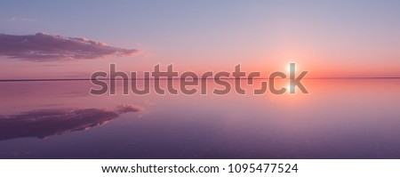 Landscape beautiful golden sunset red sky solt lake saline Elton Baskunchak. The sun sets behind the horizon #1095477524