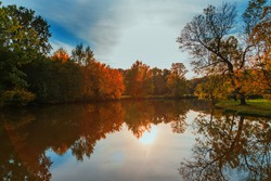 Landscape by the water. Stara Dyje river near Genoa castle in Czech republic. Trees are reflected in the river. Calm water. Colorful autumn. Beautiful clouds in the sky.