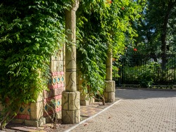 Landscape design. Beautiful garden decorative latin american stone historical pillar overgrown