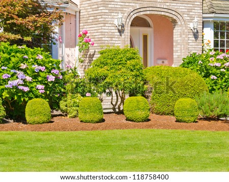 Landscape design. Nicely trimmed bushes in front of the house,  front yard