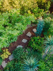 Landscape design with flower beds and path, natural landscaping panorama in home garden. Beautiful view of nice landscaped garden in residential backyard. Aerial view