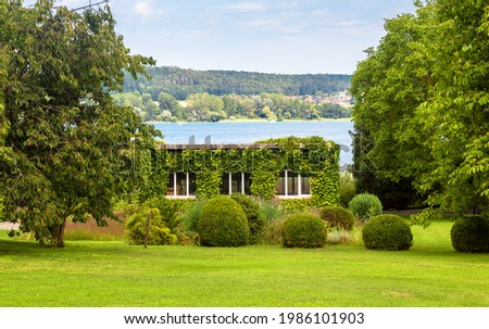 Landscape design with plants and flowers at house in Reichenau Island, Germany. Nice landscaping home garden overlooking Constance Lake (Bodensee). Scenic view of beautiful landscaped backyard. Stock photo ©