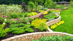 Landscape design with stones, plants and flowers at residential house. Landscaping panorama of nice home garden and lawn, scenic view of landscaped backyard. Beautiful floral landscape in summer.