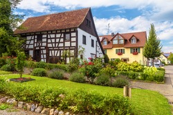 Landscape design with stones, plants and flowers at residential houses in Reichenau Island, Germany, Europe. Nice landscaping home gardens. Scenic view of beautiful landscaped street in summer.