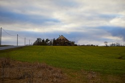 Landscape. Evening. Green-yellow field. Dried grass. Dark blue sky. Gray clouds. Road. Power line. A small house. Trees.
