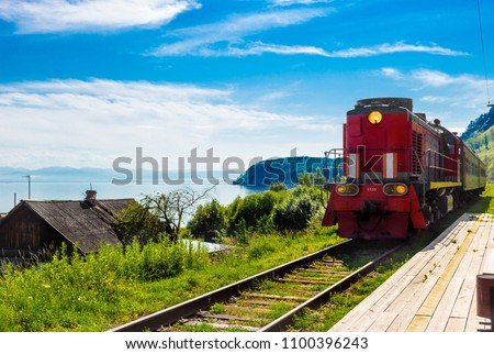 Landscape for travel with the arrival of a red train on a wooden deserted platform Trans-Siberian railway in a village on Lake Baikal in a bright summer sunny day.