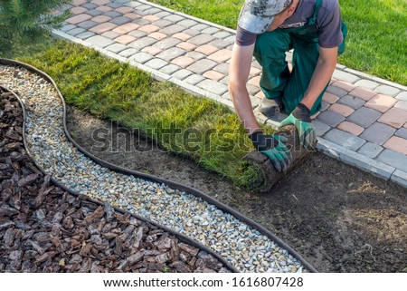 Landscape Gardener Laying Turf For New Lawn Stockfoto ©