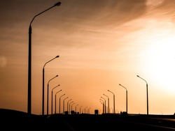 Landscape horizontal photography with a black silhouettes of a concrete lamp posts along the highway on the sunset with beautiful colorful sky and sun shining above the skyline